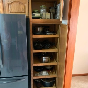Cookware in pantry cabinet and top of cabinet